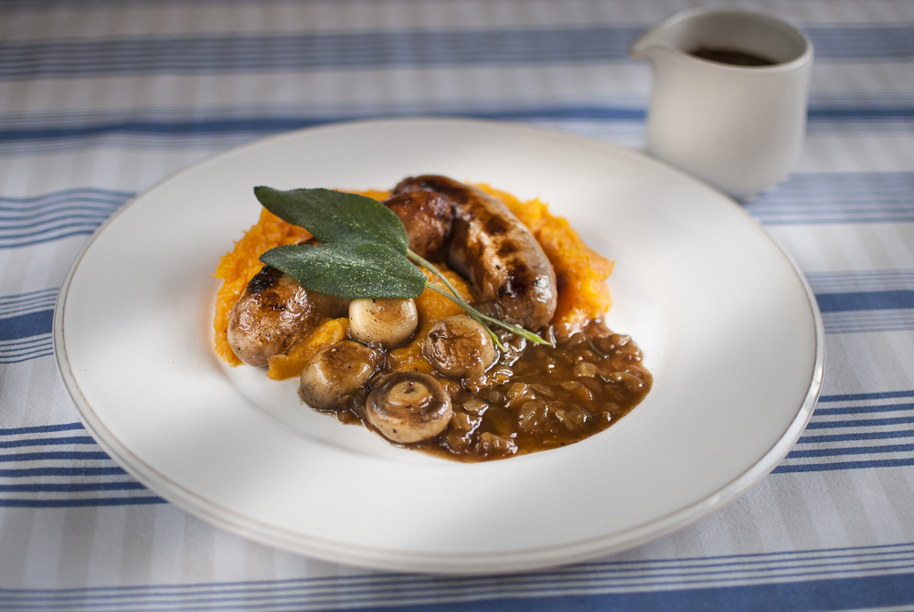 Sausages and seasonal squash make a great combo. Here they are served with sage and onion gravy to make a perfect autumn supper.