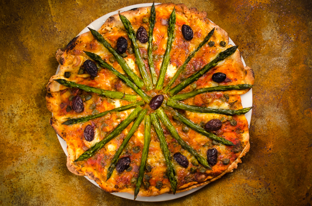 This recipe matches asparagus with a deconstructed puttanesca sauce. Surprisingly, this really works - the asparagus stands up well to the robust pizza flavours.